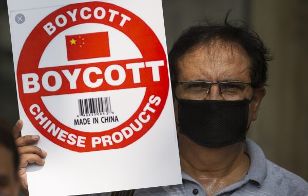 This image shows a journalist holding placard for banning Chinese products
